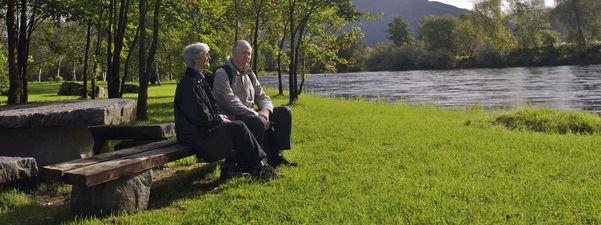 Bildet syner ein eldre mann og ei eldre kvinne sit på ein benk ved elva Jølstra i Førde. Det er midt på sommaren, med sol, grønt gras og grønt lauv på trea. Foto: Oskar Andersen