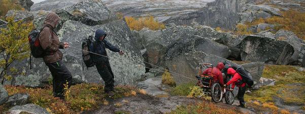 Biletet syner tre menneske som hjelper ein i rullestol å ta seg fram i ulendt terreng til fjells. Vêret er grått og glautt.