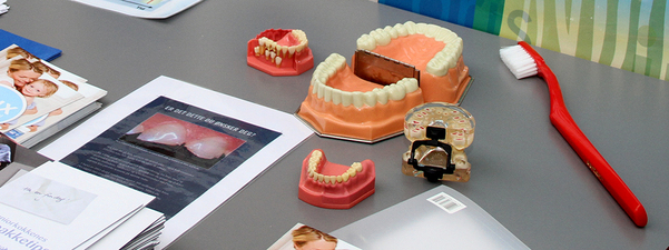 Grått bord med tre par falske tenner, brosjyrer og ein stor raud tannbørste.