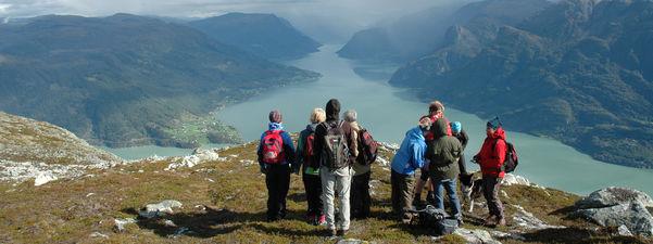 Ni personar kledde for fjelltur står på toppen av fjellet Molden i Luster og ser innover Lustrafjorden. Det er sol, men lågt skydekke. Til venstre ser vi Nes, og til høgre går vegen innover sørsida av Lustrafjorden.