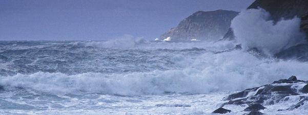 Bølgjer på uroleg sjø som slår inn mot land. Foto: Rolf Sørensen