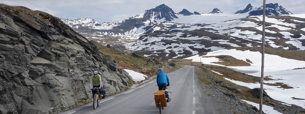 To sykkelturistar, ein på veg opp og ein på veg ned, møtest på det høgste punktet av Sognefjellsvegen, ved Fantesteinen, 1432 meter over havet. Smørstabbtindane med Smørstabbreen ruver i bakgrunnen. Foto: Werner Harstad/Statens vegvesen
