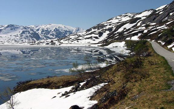 Vegen over Gaularfjellet er heilt til høgre i biletet, til høgre for eit delvis isdekt vatn. Det er blå himmel og sol, men i fjellet ligg det framleis ein del snø. Foto: Bjørn Andresen/Statens vegvesen