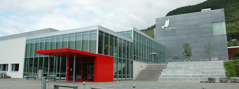 foto av Eid vidaregåande skule og Opera Nordfjord, vi ser framsida av bygget og inngang til Operaen. Grå bygning med iaugefallande raudt inngangsparti. sommar, blå himmel. foto: Sogn og Fjordane fylkeskommune