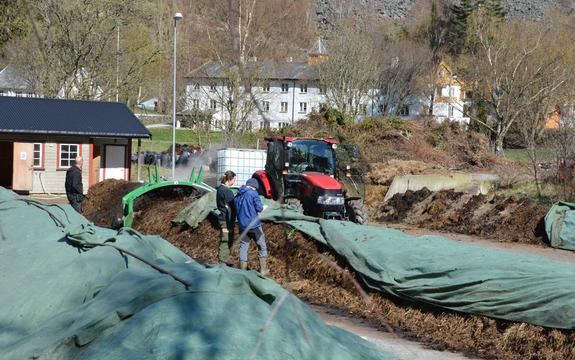 Foto som syner gardsarbeid på Sogn Jord- og Hagebruksskule i Aurland. I framkant ser vi tre personar og ein raud traktor, medan skulebygningen ruvar i bakgrunnen. Foto: Sogn Jord- og Hagebruksskule