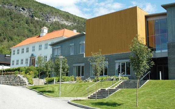 Foto av nokre av bygningane ved Firda vidaregåande skule ein sommardag med blå himmel og grønt gras. Foto: Sogn og Fjordane fylkeskommune