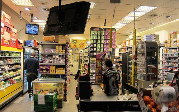 Foto som syner kasseområdet i ein daglegvarebutikk. Ein tilsett står med ryggen til i kassen, medan ein kunde er på veg inn i butikken, også han med ryggen til. Foto: Ulf Larsen/Wikipedia