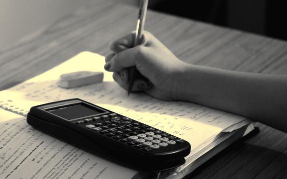 Foto som syner ei oppslått bok, med ei notatblokk oppå. Ei hand som held ein penn, kjem inn frå høgre side. På notatboka ligg det også eit viskelær og ein kalkulator. Foto: Steven S/www.flickr.com