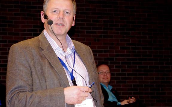 Jan Heggheim, direktør for næring, på Tiltakskonferansen i 2011. Med mikrofon framfor ein sal. Foto: Arne Monrad Johnsen/Sogn og Fjordane fylkeskommune