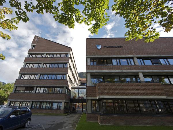 Foto av Fylkeshuset sett frå parkeringsplassen under huset. I toppen av bilete ser vi grønt lauv og blå himmel. Foto: Oskar Andersen