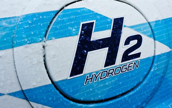 Illustrasjon som syner symbolet H2, med ordet hydrogen under. Bakgrunnen er kvit- og blåstripete. Foto: Zero Emission Resource Organisation, www.flickr.com