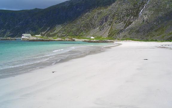 Foto frå stronda Grotlesanden i Bremanger. Sanden er nesten kvit i sola, og vi ser småbølgjene slå inn. I bakgrunnen har vi høge fjell, som skyene sig innover. Foto: Linda H. Knudsen, www.flickr.com