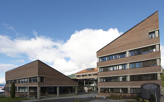 Foto av Fylkeshuset på Leikanger, under blå himmel med enkelte skyer. Biletet er teke sida med inngangspartiet, og syner store delar av huset. Foto: Oskar Andersen