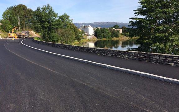 Foto som syner gang- og sykkelvegen langs Thor Solbergvegen og Kinnvegen i Florø. Biletet syner også litt av Storevatnet i bakgrunnen og muren som går langs vegen. Foto: Arild Øren