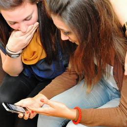 Bilde av to unge jenter som ser på ein smarttelefon.