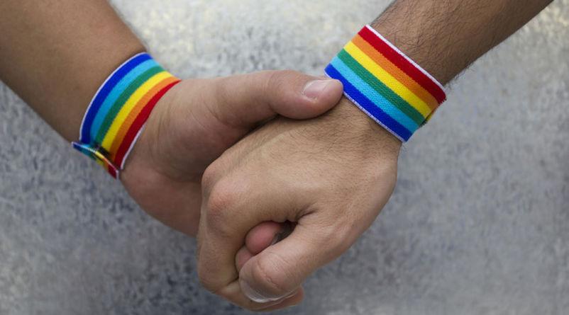 Bilete av to hender og regnbogefargar som illustrasjon på homofili.