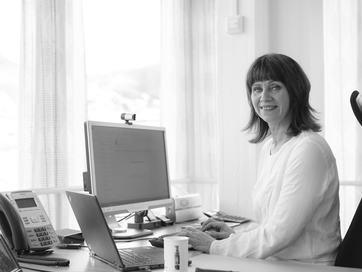 Jenny Følling sit ved pulten på sitt kontor
