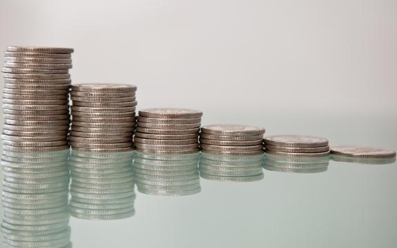 Foto av stablar av myntar som ligg på ein spegel, slik at heile speglbiletet syner òg. Foto: Tax Credits/www.flickr.com