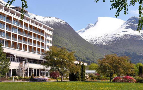 Hotellfasade med snøkledde fjell i bakgrunnen