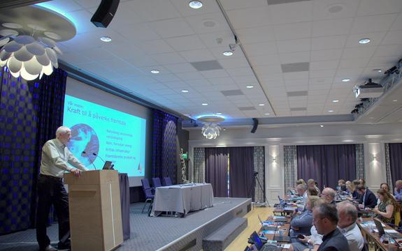 Mann står på talarstol med presentasjon på lerretet bak seg og publikum foran seg.