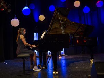Jente ved piano på scene.