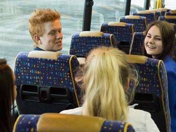 Ungdomar sit på to rader i ein buss