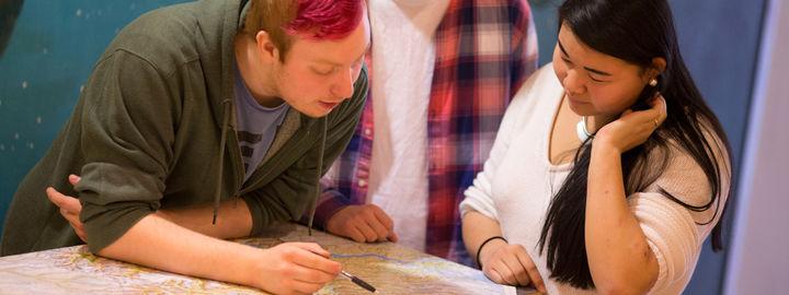 Tre elevar frå service og samferdsel studerer kart