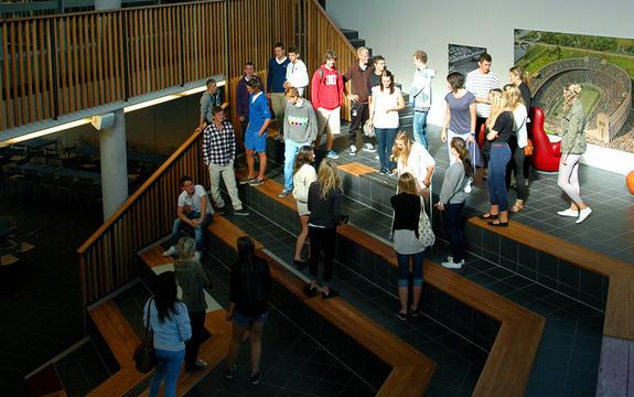 totalbilete av trapp i inngangspartiet ved Sogndal vidaregåande skule, fleire sommarkledde elevar står i trappa, både jenter og gutar.