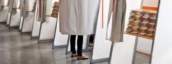 Foto som syner eit vallokale med mange avlukke. I eitt av avlukka ser vi eit par føter, og i det ved sidan av ser vi hylla med stemmesedlar. Foto: Kommunal- og regionaldepartementet.