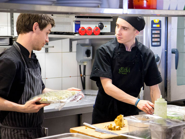Foto som syner to unge gutar på eit storkjøken. Dei er svartkledde og tilberedar mat. Foto: Charlotta Wasteson/www.flickr.com