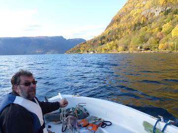 Foto som syner grunneigar Johannes Vedvik som viser fram plassen der Luster kommune vil plassere dagsturhytta si. Vedvik er i båt og peikar inn mot land, hytta skal liggje ved sjøen i Ytre Eikum.