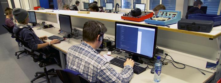 Bilete syner elevar som utfører programmering på PC