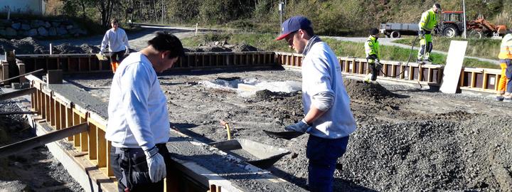 Bilete av elevar i arbeid med betong til ringmur