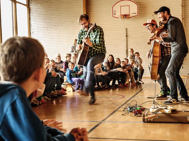 Foto av tre unge menn som opptrer under ei førestilling i Den kulturelle skulesekken. Dei spelar gitar, cello og fele, er kledde i dongeribukse og sjkorter. Framsyninga er i ein gymsal, og publikum er ungar i barneskulealder.