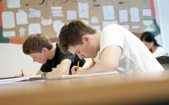 Nærbilete av to gutar som sit bøygde over bøkene i klasserommet og skriv, ein har kvit t-skjorte, den andre svart. I bakgrunnen ser vi elevarbeid på veggen og ei jente. Foto: Hordaland fylkeskommune