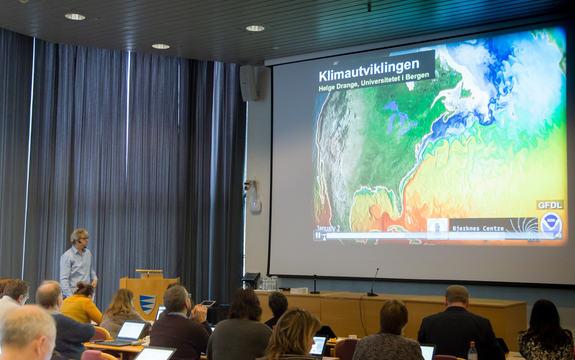 Mann presenterer powerpoint på stort lerret foran publikum