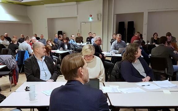 Personar sit rundt kvite bord i eit konferanselokale