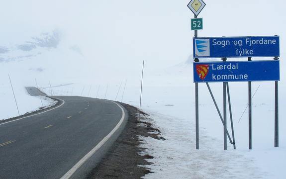 Foto frå fylkesgrensa på Hemsedalsfjellet. Til høgre i biletet ser vi fylkesskiltet for Sogn og Fjordane og kommuneskiltet for Lærdal. Til venstre i biletet er sjølve vegen. Det er snø og delvis skodde.