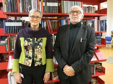 Foto av Siri Ingvaldsen og Ove Eide på Sogndal folkebibliotek. Vi ser bokhyller i bakgrunnen.