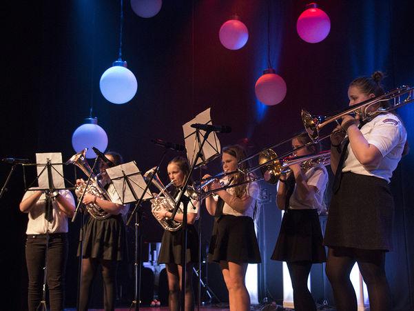 Foto av seks born og ungdomar som spelarar ulike messinginstrument på ei scene. Dei er kledde i svart og kvitt, har notestativ framfor seg, og i taket heng det raude og blå runde lampar.