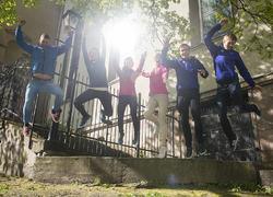 Foto av seks ungdomar som jobbar frå ein låg murkant og ned på bakken. Fire har blå og to har rosa jakkar. Dei står framfor ein beige murbygning, vi ser tre rundt dei, og gjenskin i eit vindauge gjer at det er eit veldig motlys i biletet.
