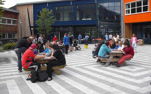 Foto teke utanfrå Stryn vidaregåande skule, ved inngangspartiet. Vi ser skulen i bakgrunnen, og på plassen framfor står det bord og benkar, der det sit mange elevar.