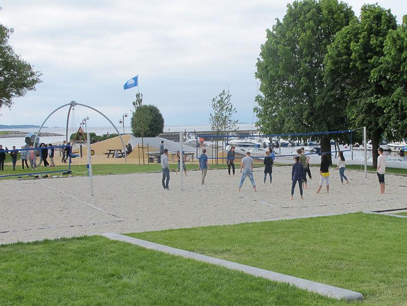 Foto som syner ungdomar som spelar sandvolleyball ein sommardag. Biletet er frå Kristiansand, det er overskya, og vi ser havet i bakgrunnen.