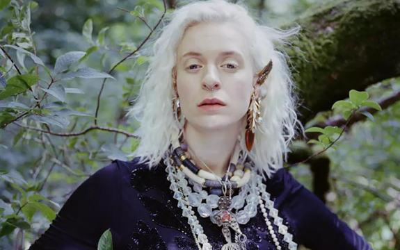 Portrettfoto av artist Thea Hjelmeland. Ho står framfor nokre busker, rett rett i kameraet, har pynt i øyrene, håret og rundt halsen og har på seg ein svart topp.
