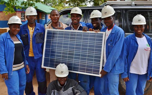 Foto som syner sju yrkesfag-elevar i Malawi som held opp ei plate. Alle er kledde i blått og har kvite hjelmar. Dei får utdanning gjennom eit prosjekt drive av Flora vidaregåande skule.