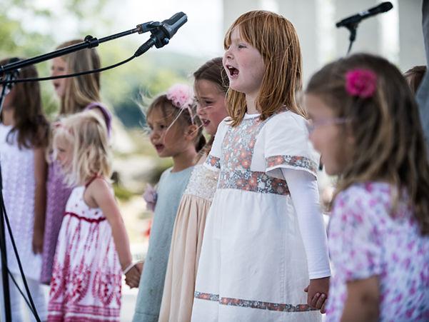 Foto av fire jenter i småskulealder som står på ei utescene og syng. Dei er kledde sommarkjolar, og fleire har blomster i håret.