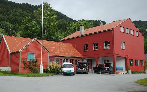 Foto av Hennebygda samfunnshus i Eid kommune. Bygget er raudt, og det står tre bilar parkerte framføre.