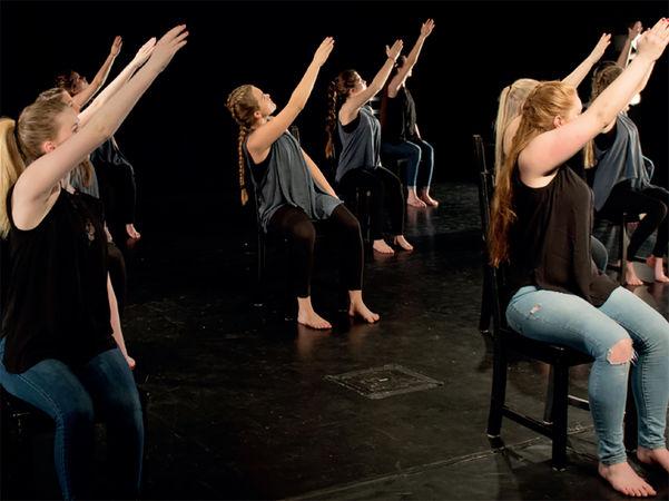 Foto som syner danseelevar på Firda vidaregåande skule. Det er eit mørkt rom, og dansarane sit på stolar. Alle er kledde i dongeribukse eller svart bukse og mørk topp. Og alle held høgrearmen oppover mot venstre.