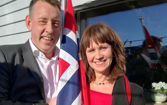 Foto av fylkesordførar Jenny Følling og ordførar i Selje, Stein Robert Osdal. Dei står framfor ein kvit husvegg, har sola i ansiktet og det norske flagget mellom seg.