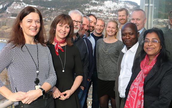 Foto som syner deltakarane på eit samarbeidsmøte mellom fylkeskommunen, Fylkesmannen, UDI, IMDi, KS og Nav. Dei er stilte opp på ein balkong på Statens hus, og i bakgrunnen ser vi Leikanger.